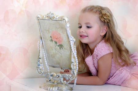 Beautiful little girl looking to retro mirror