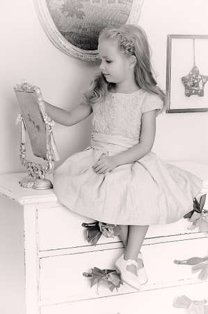 antique mirror: Beautiful little girl looking to retro mirror
