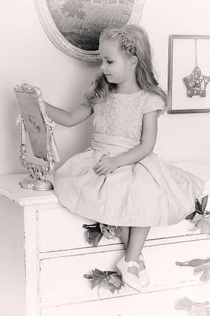 Hermosa niña mirando al espejo retro