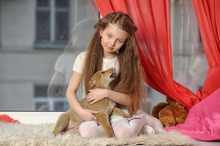 little girl with a puppy in her arms photo
