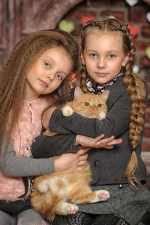 Girls holding cat photo