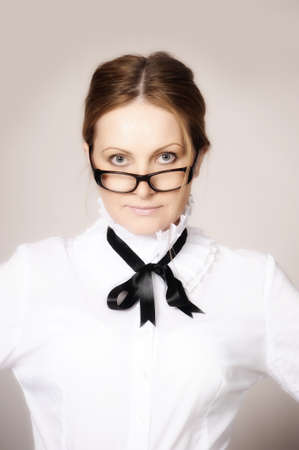 woman in a white blouse with a bow and glasses photo
