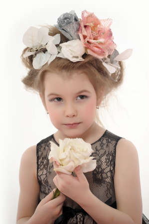 little girl with flowers on her head and a white rose in her hand photo