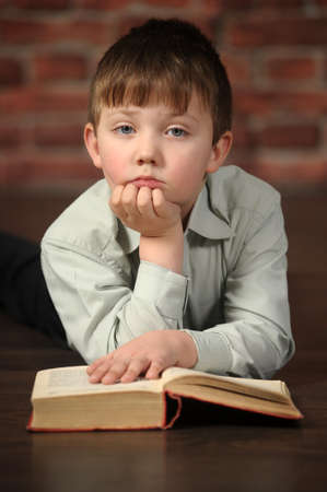 Ponderer boy with the book lies photo