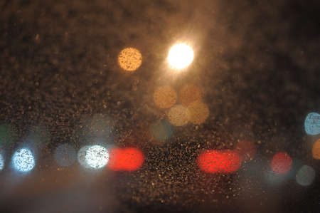 Raindrops over window glass closeup  blurred night background with coloured lights photo