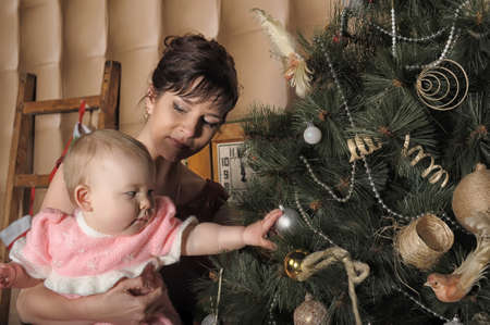 mom with a little girl in the arms of a Christmas tree photo