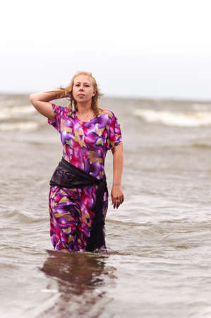 woman walking in the water along the beach Stock Photo - 18309141