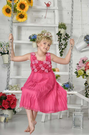 young girl on a swing with flowers photo