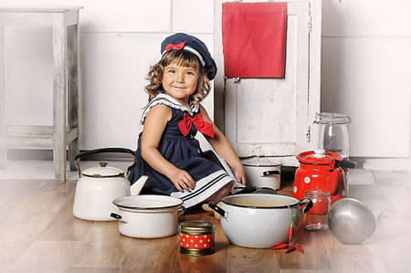 little girl in the kitchen of cookware photo