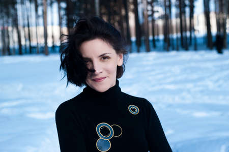 Portrait of a young dark-haired woman on a background of snow-covered landscape photo