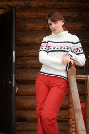 young woman in a sweater and ski pants near a wooden house photo