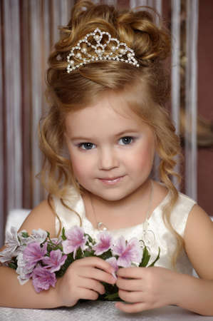 little princess in a white dress with a tiara on her head