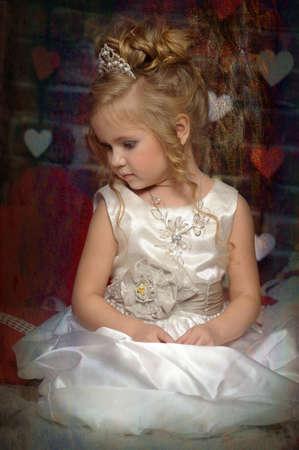 pequeña princesa en un vestido blanco con una tiara en la cabeza