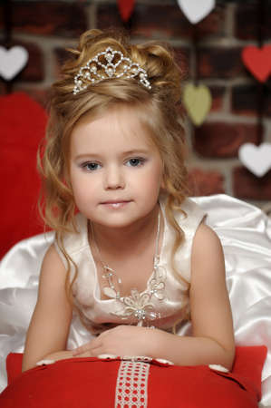 marriageable: little princess in a white dress with a tiara on her head