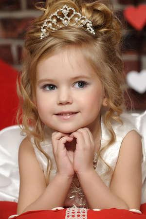 kleine prinses in een witte jurk met een tiara op haar hoofd Stockfoto