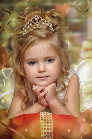 little princess in a white dress with a tiara on her head photo