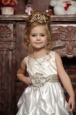 debutante: little princess in a white dress with a tiara on her head