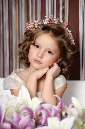 Beautiful little girl in wreath of pink flowers photo