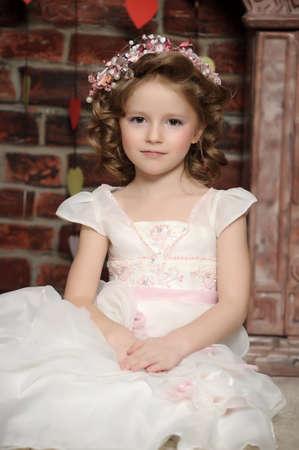 Beautiful little girl in wreath of pink flowers