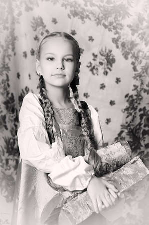 Retro picture of girl in national costume with Russ wood in his hands photo
