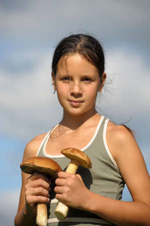 girl with two mushrooms in the hands of Stock Photo - 28610209