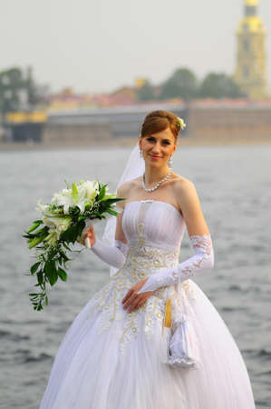 happy bride with a bouquet of white lilies photo