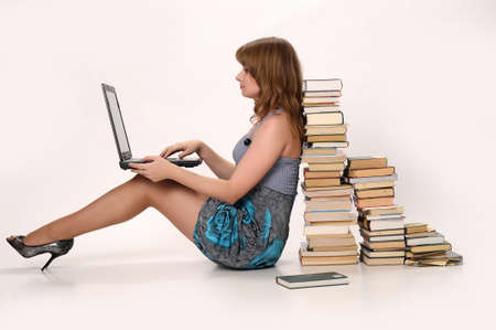 girl with a laptop next to a pile of books