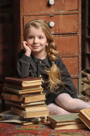 niña con un libro en la biblioteca antigua Foto de archivo