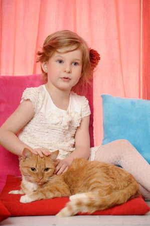 little girl hugging a big red cat photo
