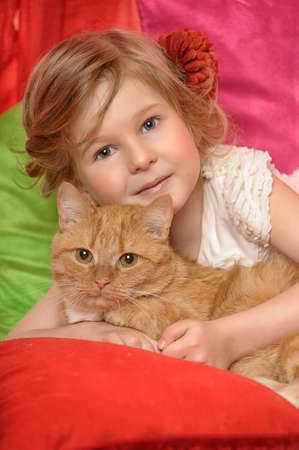 little girl hugging a big red cat