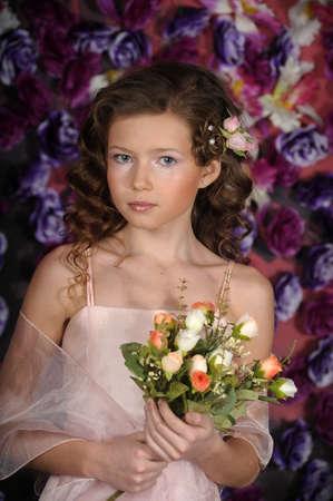 ni�a en un vestido de color rosa sobre un fondo de un arco de flores photo