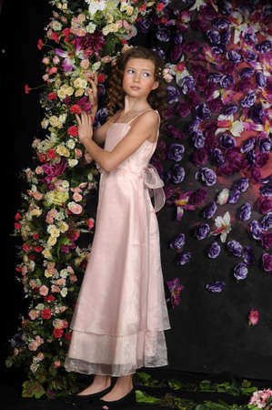 girl in a pink dress on a background of an arch of flowers Stock Photo - 19121546