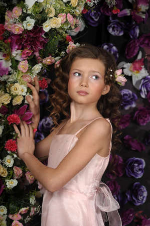 girl in a pink dress on a background of an arch of flowers Stock Photo - 19121545