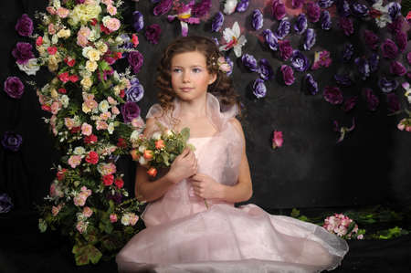 girl in a pink dress on a background of an arch of flowers Stock Photo - 19121542