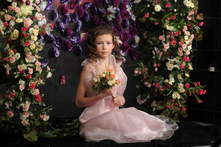 girl in a pink dress on a background of an arch of flowers photo