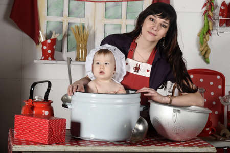 young mother and baby in a pan in the kitchen photo