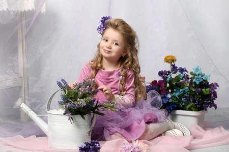 charmant klein meisje met een gieter en bloemen Stockfoto