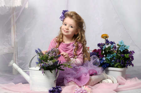 charming little girl with a watering can and flowers Standard-Bild