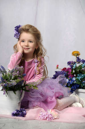 charming little girl with a watering can and flowers photo