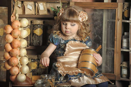 a little girl dressed in retro style on the old kitchen Stock Photo - 19204202