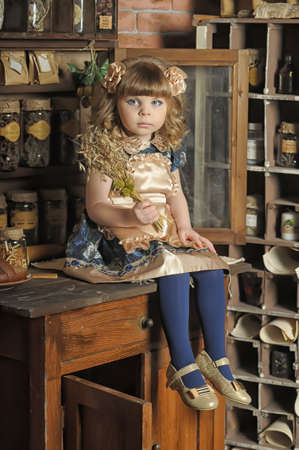a little girl dressed in retro style on the old kitchen Stock Photo - 19204207