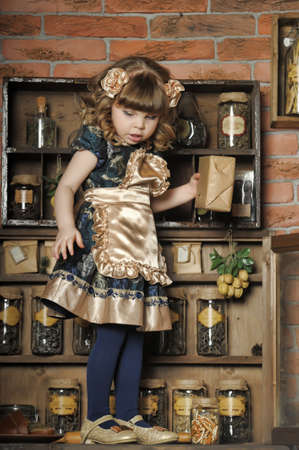a little girl dressed in retro style on the old kitchen Stock Photo - 19204199