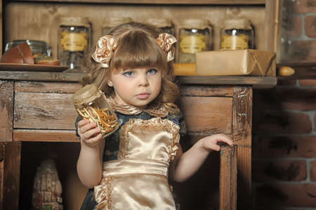 a little girl dressed in retro style on the old kitchen Stock Photo - 19204196