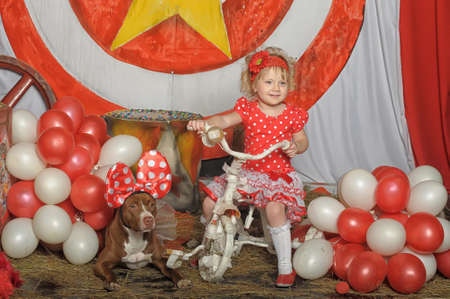 girl on a tricycle with a dog and balloons photo
