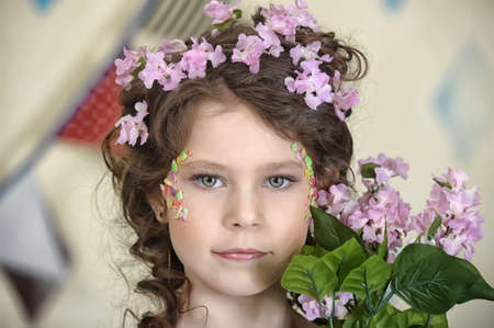 portrait of a girl with flowers in her hair, and in the hands of Stock Photo - 19339009