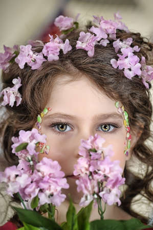 portrait of a girl with flowers in her hair, and in the hands of Stock Photo - 19339010