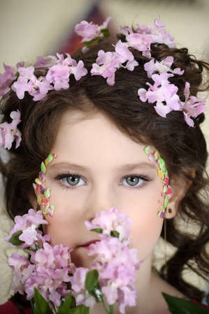 portrait of a girl with flowers in her hair, and in the hands of Stock Photo - 19339011