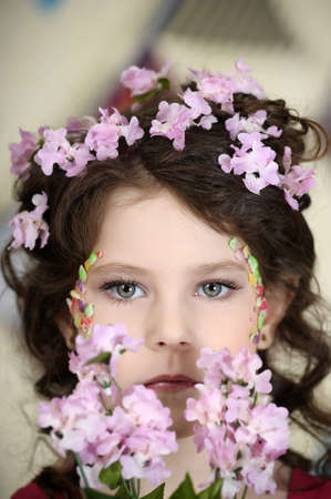 portrait of a girl with flowers in her hair, and in the hands of Stock Photo - 19397329