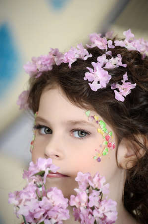 portrait of a girl with flowers in her hair, and in the hands of Stock Photo - 19397323