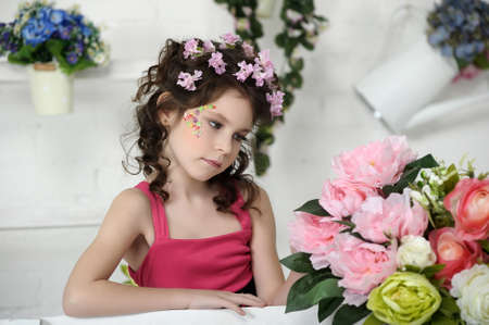 portrait of a girl with flowers in her hair, and in the hands of Stock Photo - 19397321